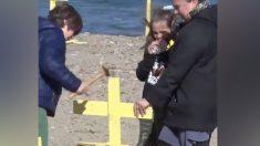 Menores clavando cruces amarillas en una playa de Gerona