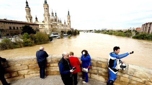 Varias personas observan el paso del río Ebro por el Puente de Piedra de Zaragoza (Foto: Efe).