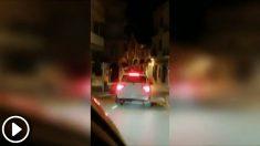 Dos chicas bailan sobre un coche en marcha con matrícula alemana en las calle de Jávea (Alicante).