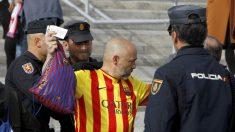 Miembros de la Policía cachean a un aficionado del Barcelona. (EFE)