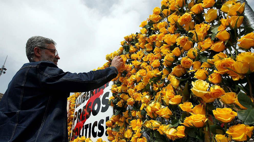 Carles Riera, portavoz de la CUP, coloca rosas amarillas en un cartel por los golpistas presos. (EFE)