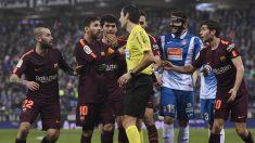 Los jugadores del Barcelona presionan al árbitro en un partido contra el Espanyol. (AFP)