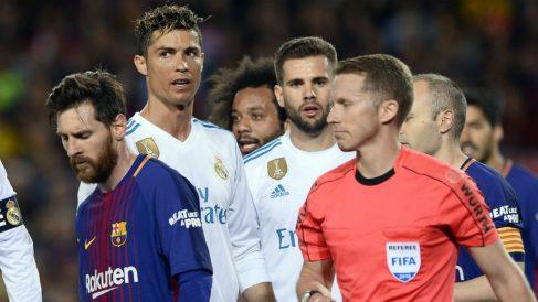 Messi, junto a Hernández Hernández en el Barcelona-Real Madrid del Camp Nou. (AFP)