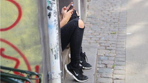 Una adolescente consulta las redes sociales en su teléfono móvil.