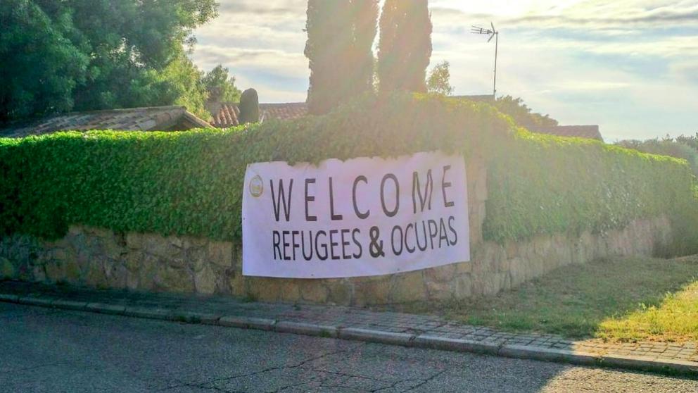 Pancarta de «Bienvenidos refugiados y ocupas? en el casoplón madrileño de Iglesias y Montero