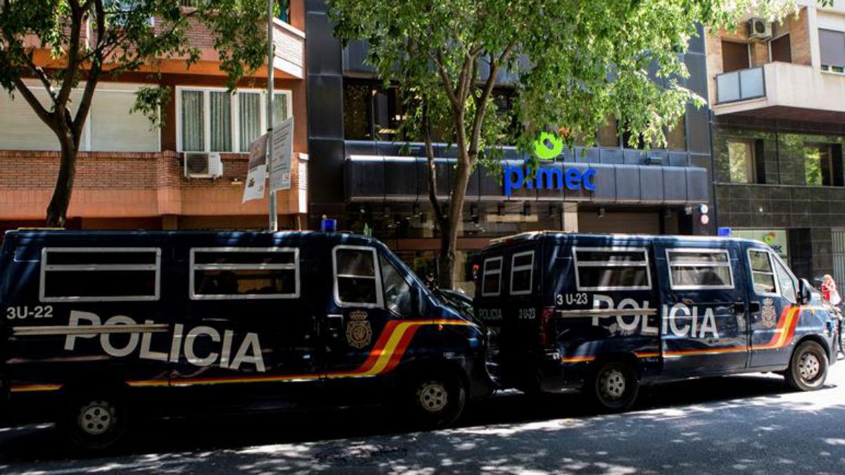Furgones de la policía la custodian la sede de la patronal de la pequeña y mediana empresa de Cataluña (PIMEC), durante los registros efectuados esta mañana por la UDEF en una macrooperación contra la Diputación de Barcelona por un presunto fraude de subvenciones (EFE).