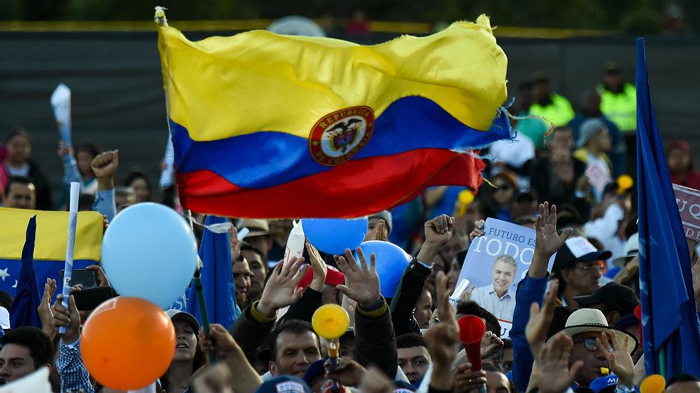 Una bandera colombiana preside un mitin de campaña del uribista Iván Duque ante las presidenciales. (AFP)