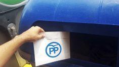 Las juventudes del PDeCAT tiran sobres del PP al contenedor azul.