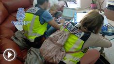 Agentes de policía revisan el material pedófilo encontrado en poder del detenido.