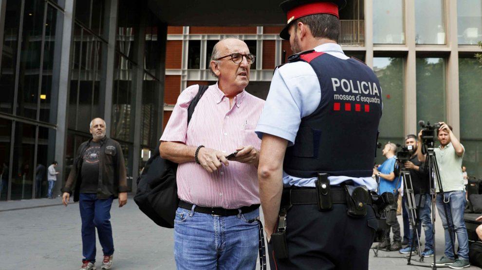 Jaume Roures conversa con un Mosso d'Esquadra ante la sede de Mediapro. (Foto: EFE)