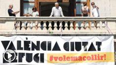 El alcalde de València, Joan Ribó (c) , se asoma al balcón de la Plaza del Ayuntamiento tras la instalación de una gran pancarta con el lema «Valencia, ciudad refugio». (Foto: Efe)