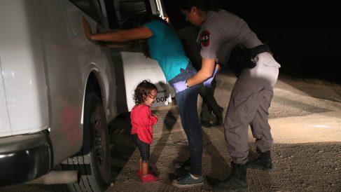 Una niña hondureña llora desconsolada mientras una agente de Nuevo México cachea a su madre tras detenerla en la frontera. (Getty)