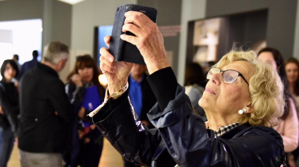 Manuela Carmena fotografiando con su teléfono móvil. (Foto. Madrid)
