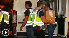 Agentes de policía cargan en un furgón documentación requisada durante los registros.