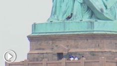 Una mujer escala la Estatua de la Libertad.