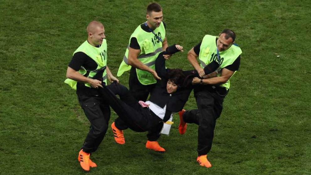 Los miembros de la seguridad del estadio sacan del campo a las Pussy Riot.