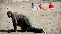 Un inmigrante llegado en patera a las costas españolas se arrastra por la playa ante unos bañistas. (EP)
