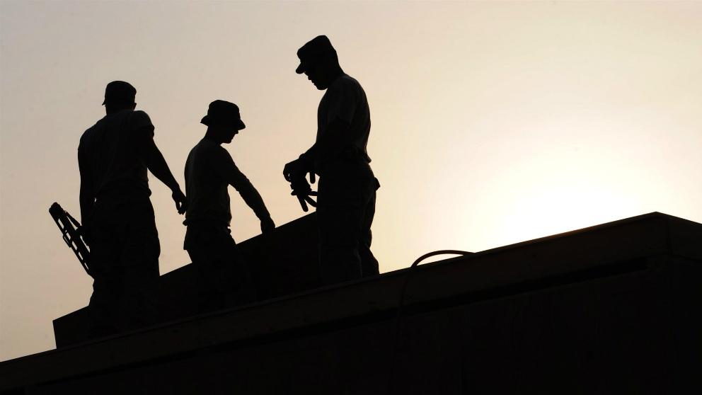 Operarios trabajando sobre un tejado en plena ola de calor. (EP)