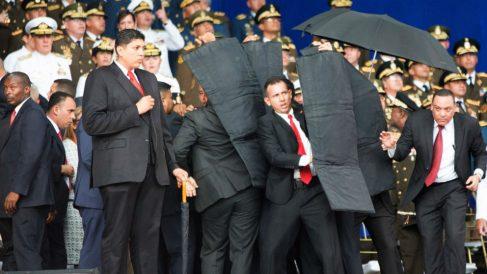 Los escoltas despliegan un escudo antibalas para proteger a Maduro durante el desfile.