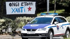 Una patrulla de la Ertzaintza pasa delante de una pancarta en homenaje al etarra Santi Potros. (Foto: EFE)