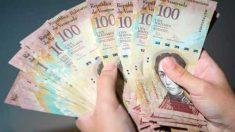 Un venezolano cuenta un enorme fajo de billetes de 100 bolívares. (ENP)