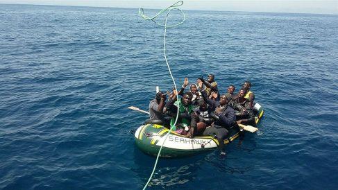 Varios inmigrantes reciben una cuerda desde el buque de Salvamento Marítimo que los rescata. (EP)