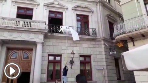 Militantes de Ciudadanos retiran la propaganda independentista de la fachada del Ayuntamiento de Reus.
