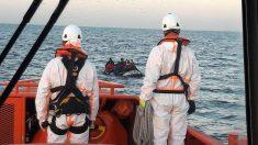 Dos trabajadores de Salvamento Marítimo rescatan una lancha llena de inmigrantes subsaharianos. (EP)s