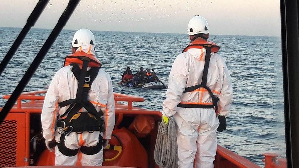 Dos trabajadores de Salvamento Marítimo rescatan una lancha con inmigrantes subsaharianos. (EP)s