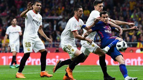 Coutinho pelea por un balón con jugadores del Sevilla. (Getty)