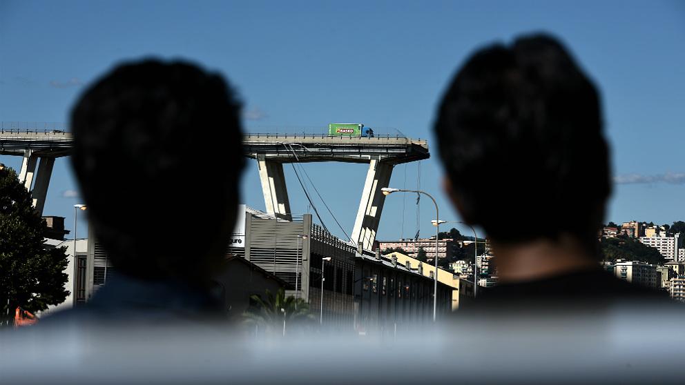Dos vecinos observan desde lejos la sección caída del viaducto de Génova. (AFP)