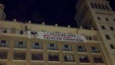 Un grupo de Mossos d'Esquadra se descuelga por la fachada de un edificio en Plaza Cataluña de Barcelona para descolgar una pancarta contra el Rey Felipe VI.