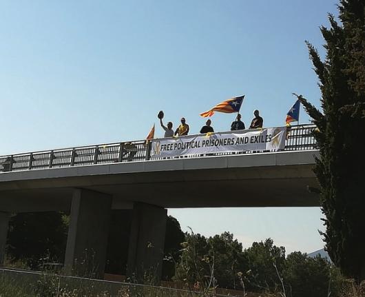 Los separatistas con la pancarta minutos antes de ser retirada por los gendarmes .