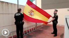 Policías locales de Abrera (Barcelona) izan la bandera de España  al son del himno nacional.