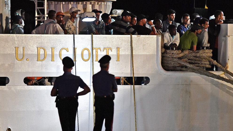 Dos policías vigilan el buque de la Guardia Costiera italiana 'Diciotti', repleto de inmigrantes a la espera de desembarcar. (AFP)
