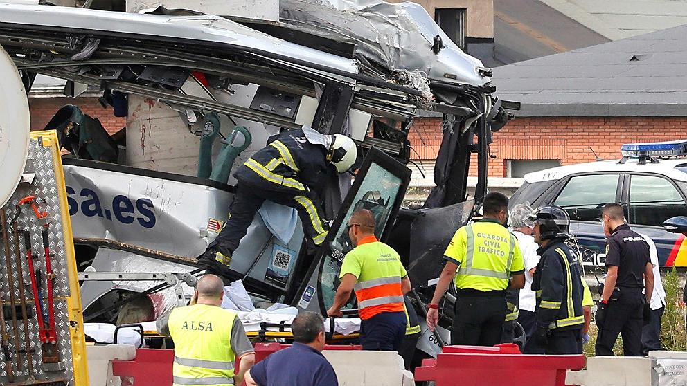 Operarios de Emergencias y de la compañía Alsa trabajan en los restos del autobús siniestrado en Avilés. (EFE)