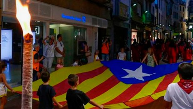 Un grupo de niños abriendo la marcha de antorchas de Tarrasa portando una gran bandera independentista