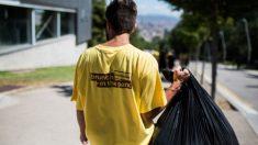 Un voluntario con una camiseta de Brunch In The Park con una bolsa de basura.