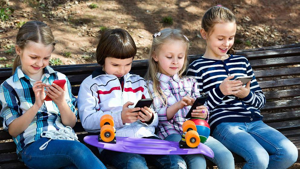 Una niñas sentadas juntas jugando cada una con su teléfono móvil. (EP / iStock)