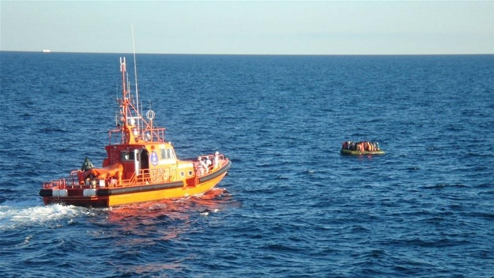 Una embarcación de Salvamento Marítimo rescatando una patera con inmigrantes en el Estrecho.