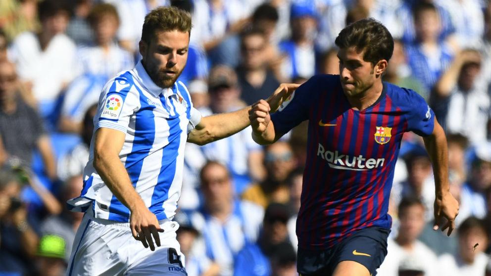 Illarramendi y Sergi Roberto disputan un balón en el Real Sociedad – Barcelona. (AFP) | Liga Santander: Real Sociedad – Barcelona | Partido de fútbol hoy en directo