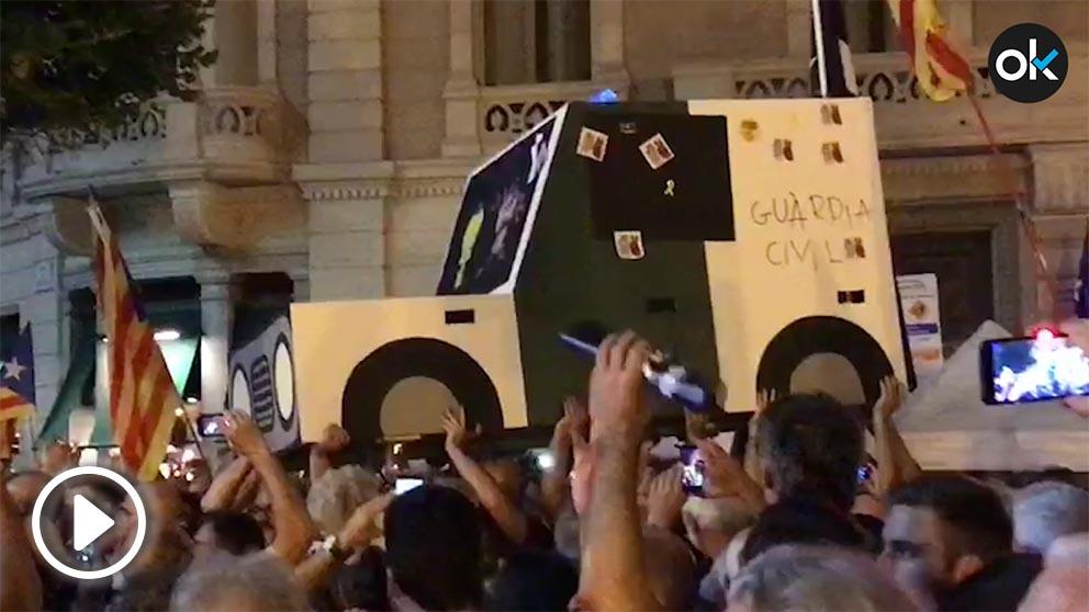 Manifestantes con una réplica de cartón de uno de los coches de la Guardia Civil destrozados hace un año.