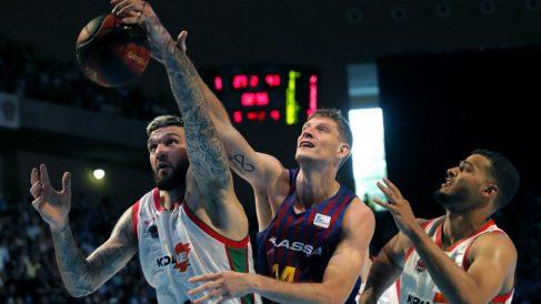 Pustovny pelea un balón con Janning y Shields durante el Barcelona – Baskonia. (EFE)