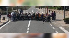 Varios ancianos en silla de ruedas cortando una carretera con motivo del 1-O