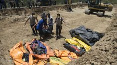 Voluntarios trasladas cadáveres a una fosa común donde se entierran a los muertos para evitar la propagación de enfermedades. Foto: AFP