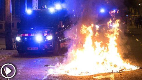 Un furgón de los Mossos pasa junto al fuego durante los altercados al finalizar la movilización convocada por la ANC y otras entidades independentistas con motivo del primer aniversario del 1-O (Foto: Efe)