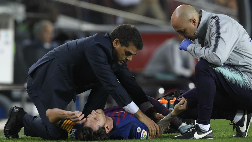 Messi es atendido por los médicos tras lesionarse el codo. (AFP)