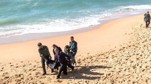 Agentes de la Guardia Civil trasladan el cadáver de un inmigrante (Foto: EFE).