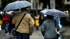 Dos ciudadanos con sus paraguas.