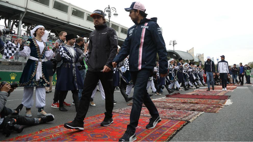 Fernando Alonso y Checo Pérez pasean por el paddock en una imagen reciente. (Getty)